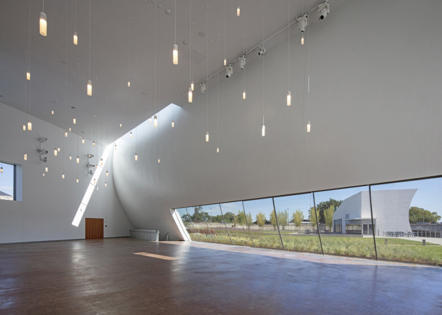 Interior image of white curved walls with light cutout in corner, fairy-like lights dangle from ceiling