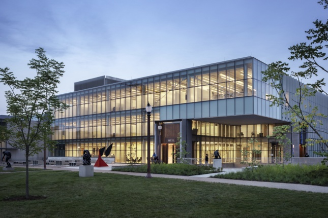 Twilight view of glass-clad academic building with sculpture garden on the Washington University campus