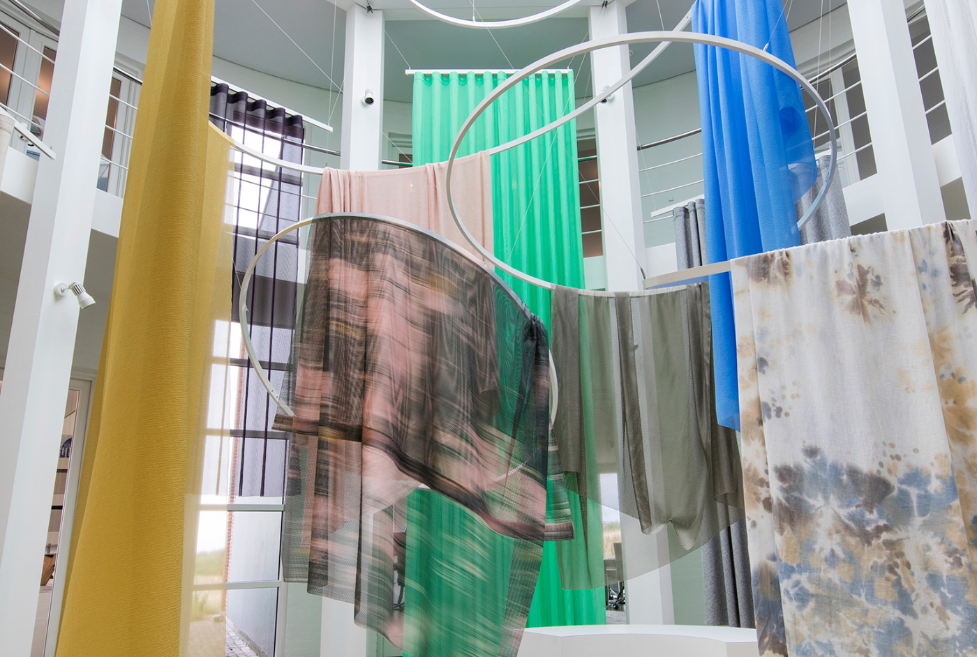 Different fabrics from Kvadrat suspended from metal rings