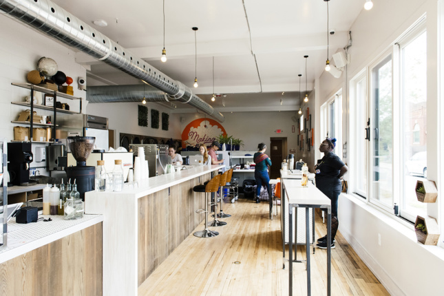 A cafe with light wood and white accents that opens onto a laundromat, part of Detroit Design 139