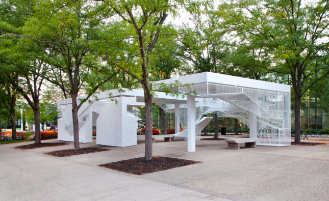 Installation view of a white metal pavilion with open bars
