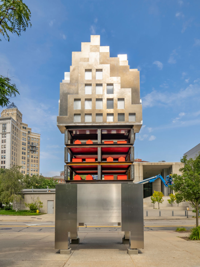 A 25-ft tall metal sculpture stands upright on a wide sidewalk. The sculpture resembles an abstracted form of a high rise building and featueres windows of various sizes. The middle of the sculpture contains a cage-like section made of metal beams and it holds multiple red house-shaped forms.