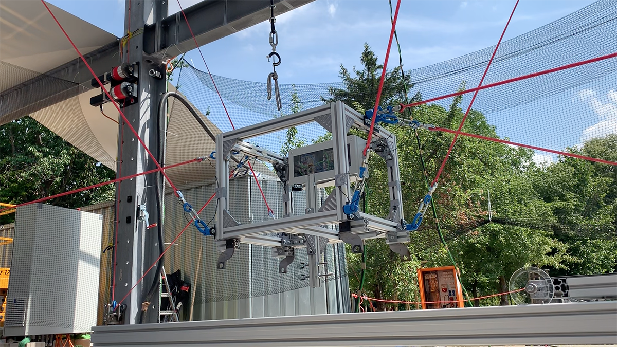 A robot in the form of a metal box is attached to various red cables and suspended a few feet in the air.