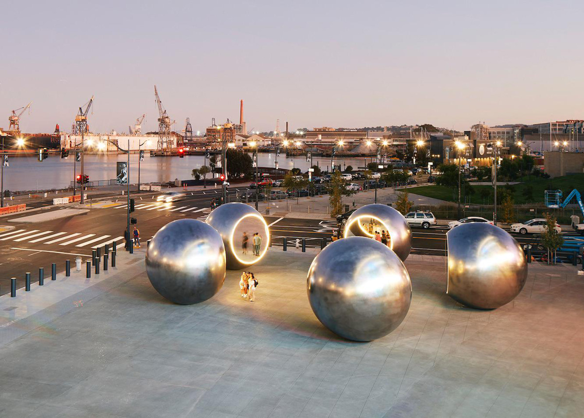 Bayside plaza with five shiny steel balls arranged in circle each lit up by ring of lights, designed by Olafur Eliasson