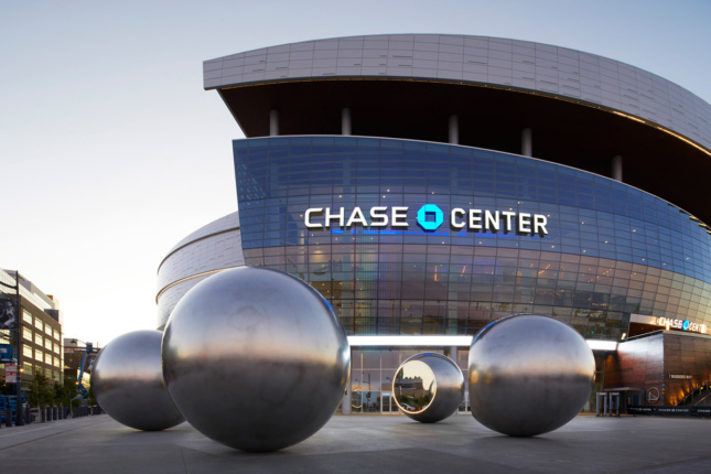 Photo of glass-clad arena building with silver spheres arranged on plaza in front