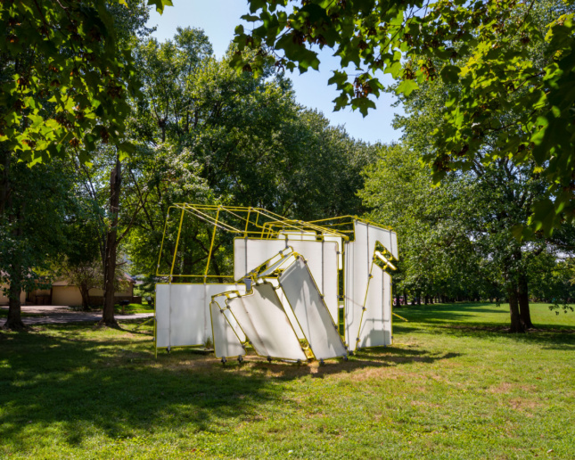 A white and yellow pipe pavilion below a grove of trees