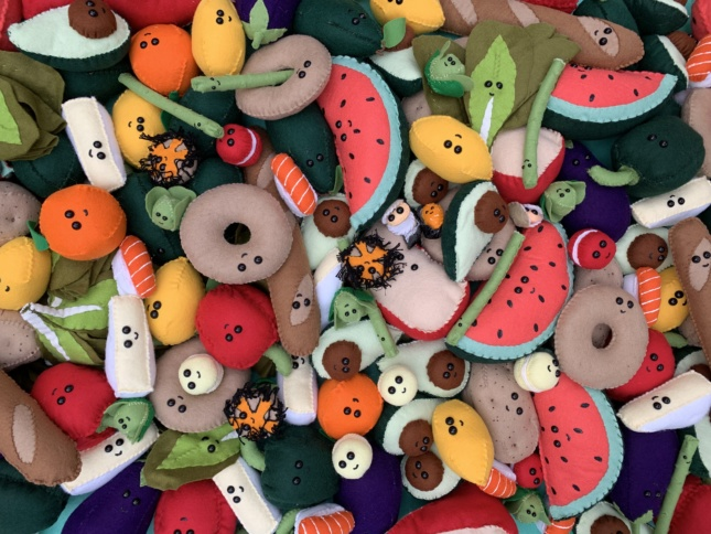 A pile of colorful foods with smiley faces and eye balls, completely made out of felt.