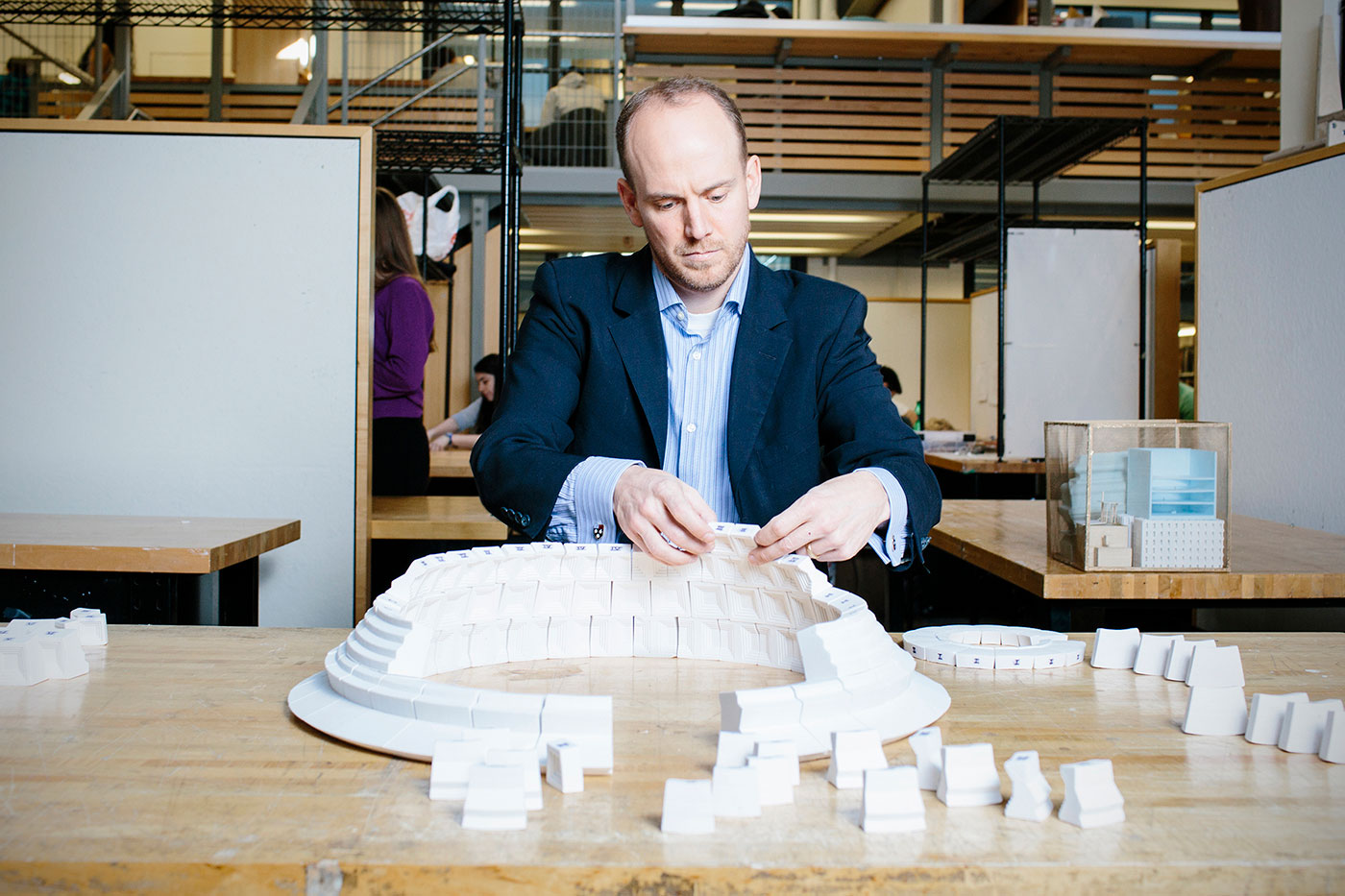 Man assembles a large architectural model on a table inside a classroom