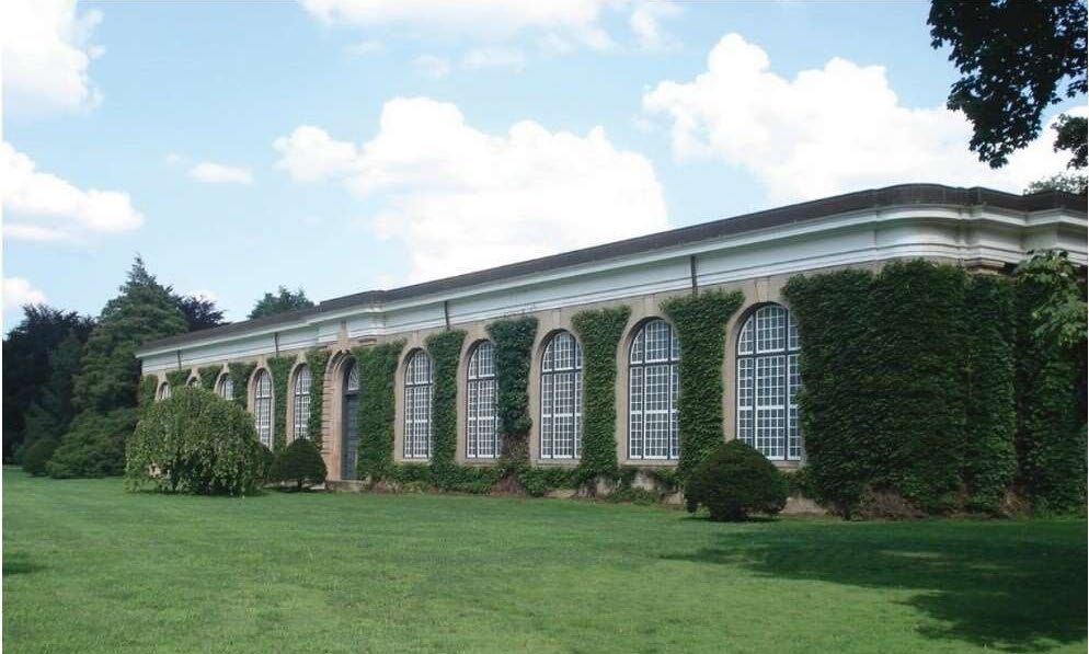 Exterior photo of the Orangerie, a historic brick building covered in ivy
