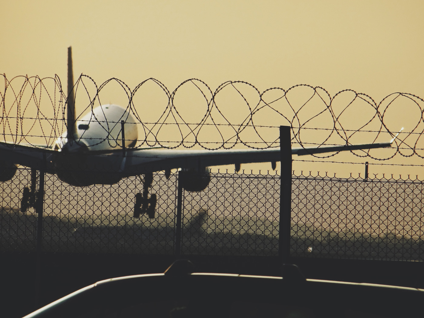 Photo of a plane taking off behind a fence at Heathrow Airport