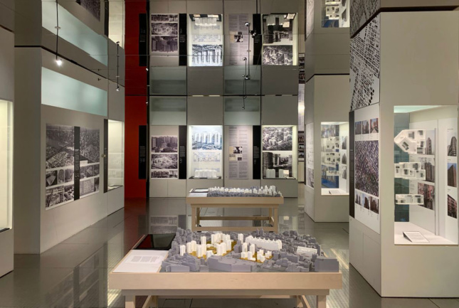 A photograph of a museum gallery filled with architectural models on a table and photographs on the wall.
