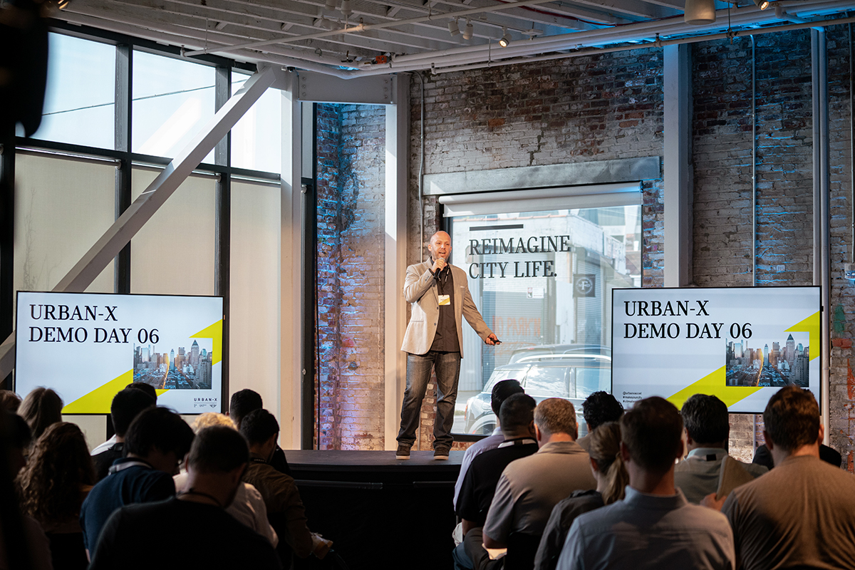 A person stands on a stage in front of two monitors while an audience looks on at Urban-X
