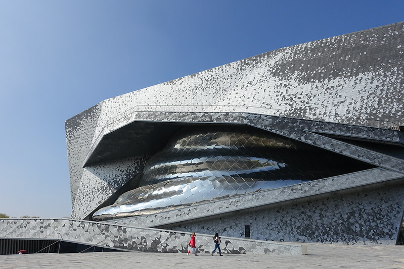 Exterior shot of curvaceous and shiny concert hall against blue sky