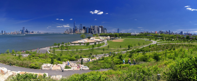 A park abutting the river with Manhattan in the background