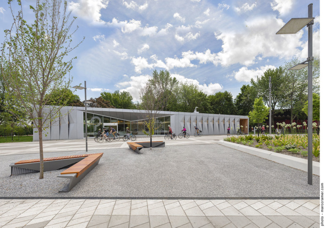 A small building with a metal facade sits in a concrete paved park surrounded by trees.