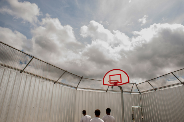 Inmates looking towards the sky in a prison basketball court