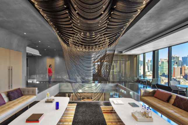 Interior of a concrete office with a bead curtain, designed by Aaron Schiller