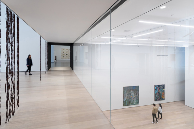 Image of glass wall separating two floors of gallery space