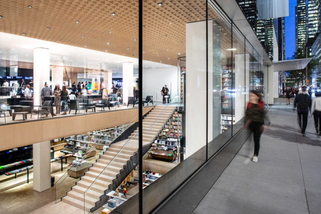 Image of woman walking on sidewalk looking at MoMA design store featuring a double-height room with large black steel stair