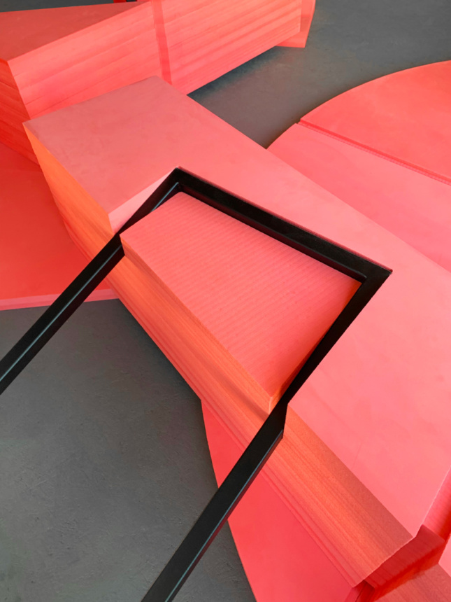 Red foam blocks cut into by steel rectangles