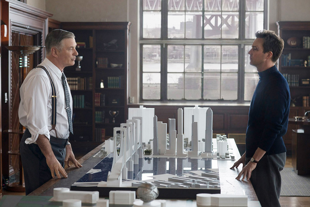 Image from Motherless Brooklyn film where Edward Norton and Alec Baldwin stare across a table with architectural models