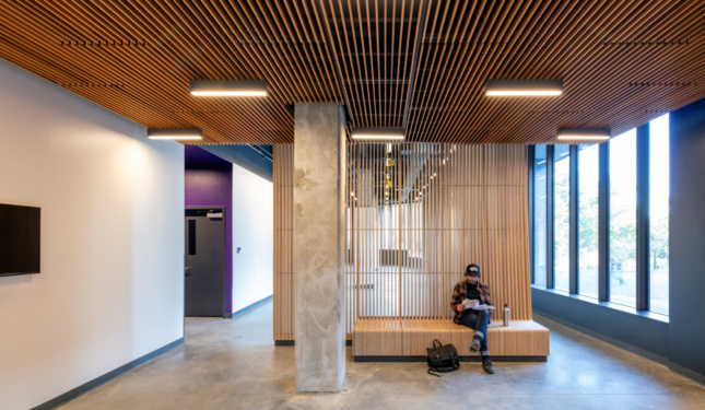 Students in a concrete lobby on timber furniture