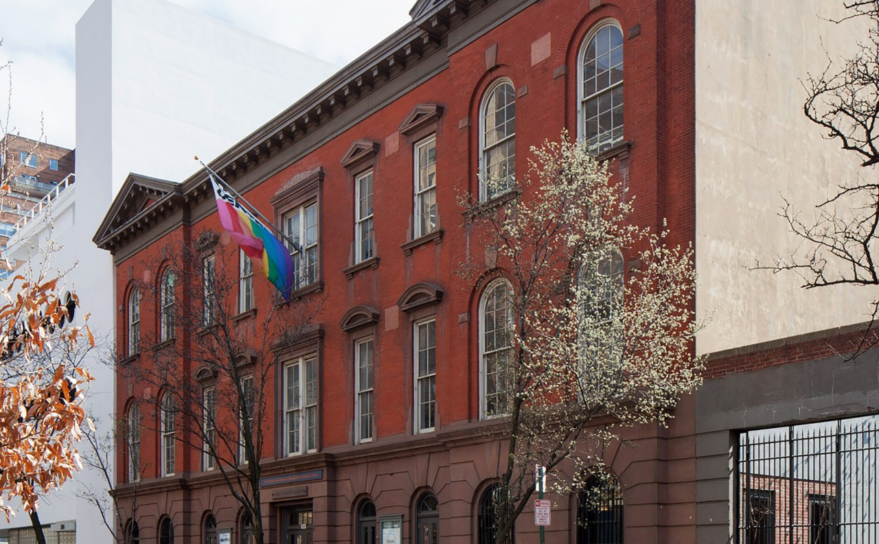 A perspective photo of a brick building on a tree lined street. A rainbow flag flies above the building's entrance.