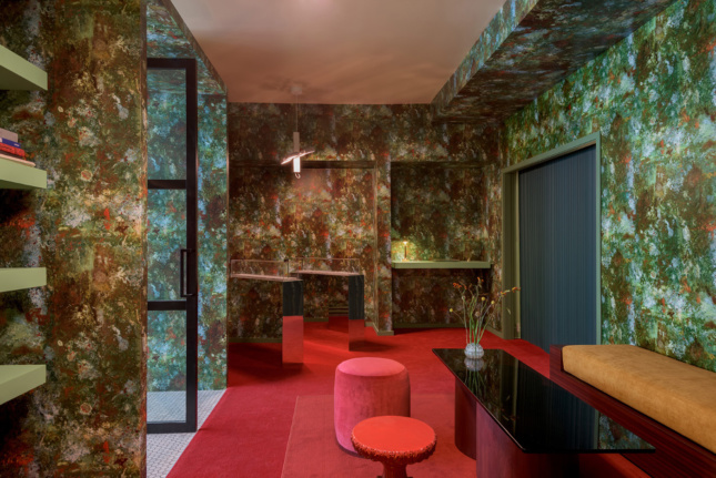 Interior of a retail space with a mottled green wallpaper