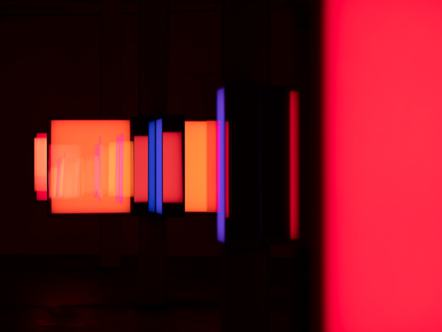 Image of pitch black room with warm-colored rectangular surfaces lit up next to one another