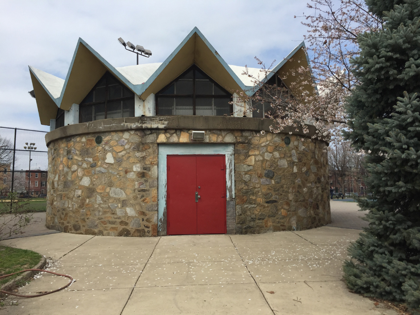 Photo of the Columbus Square pavilion, a small, circular structure with thick stone walls, a single red door, and an angular roof.