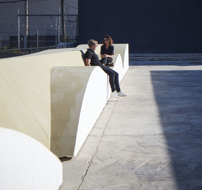 Two people sit on a wave-shaped concrete bench.