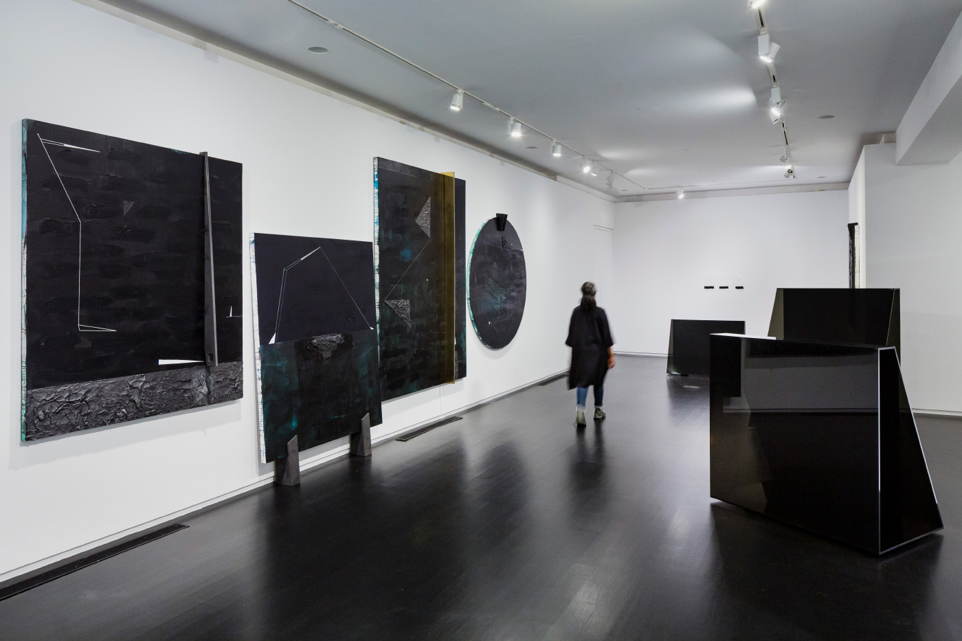 Installation view of black paintings by Torkwase Dyson on a white background