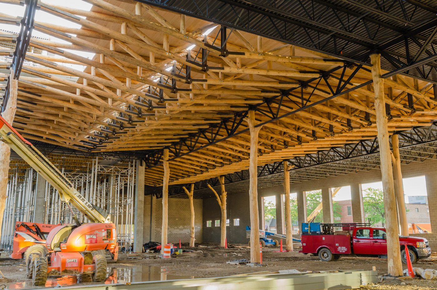 Very tall timber trusses being installed in a WholeTrees grocery store