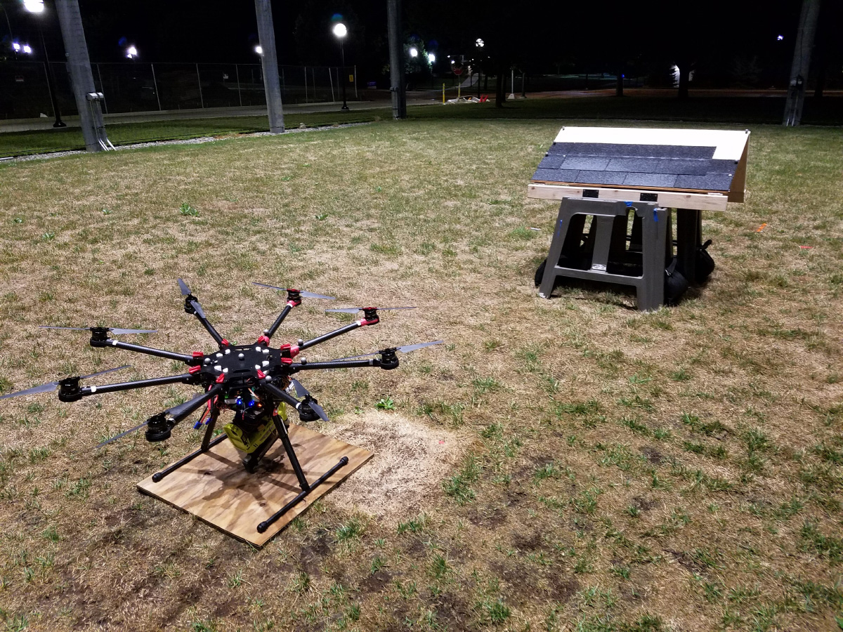 A drone on a lawn in front of a miniature roof on the ground.