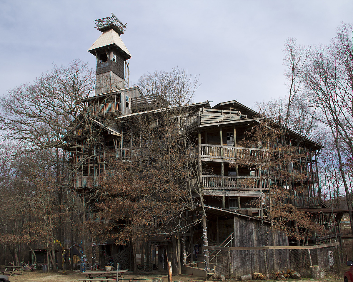 A large wooden structure with a tower set in some trees.