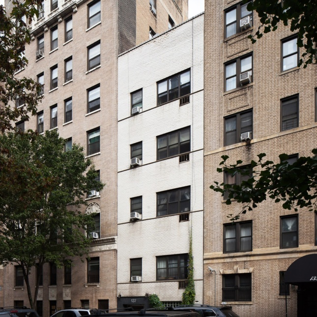 A photo of a modern, white, brick apartment building surrounded by taller apartment buildings on a tree-lined street.