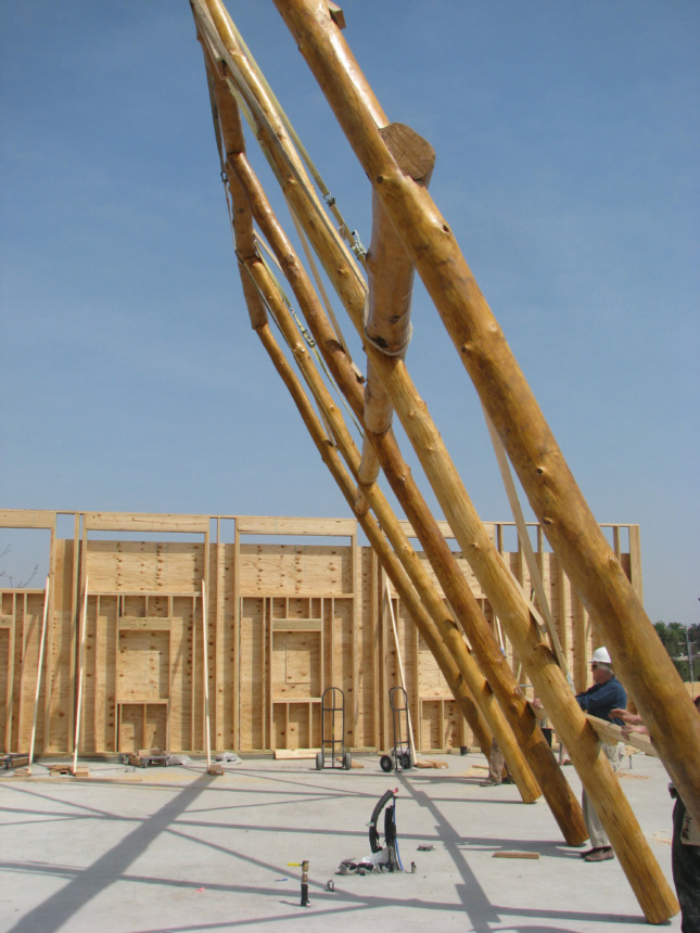 A large timber frame being raised into place
