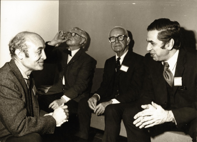 A black and white photo of four men talking and drinking, including Isamu Noguchi