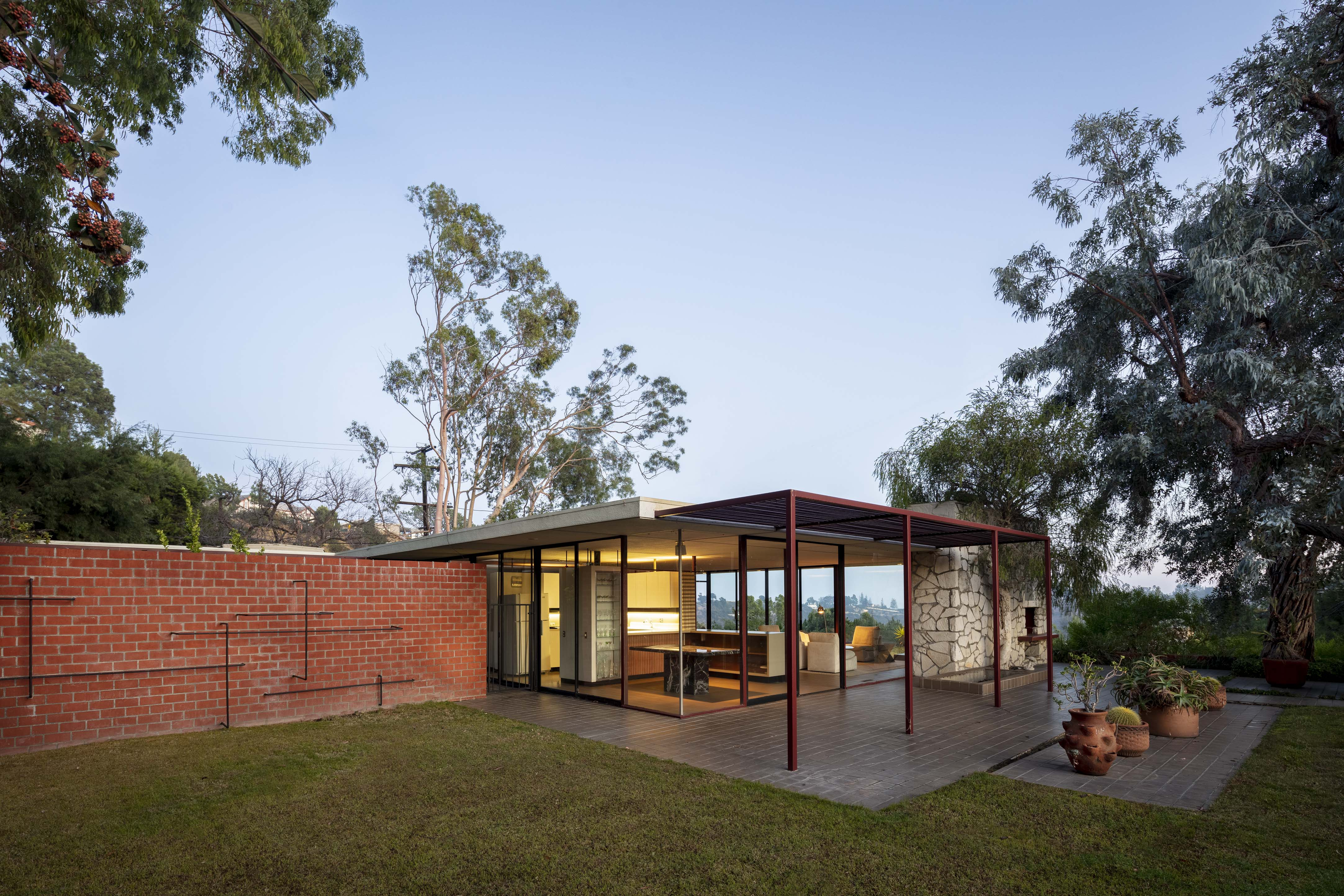 A small, flat roofed house sits on a hill overlooking los Angeles