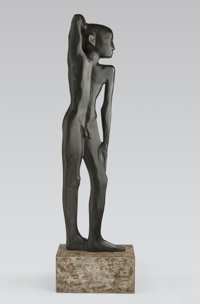 A sculpture of a young black boy standing with his arm draped over his head