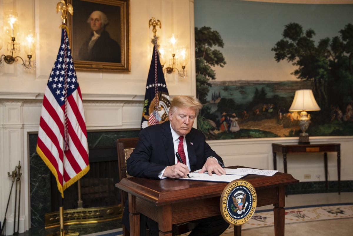 Image of President Trump signing a letter