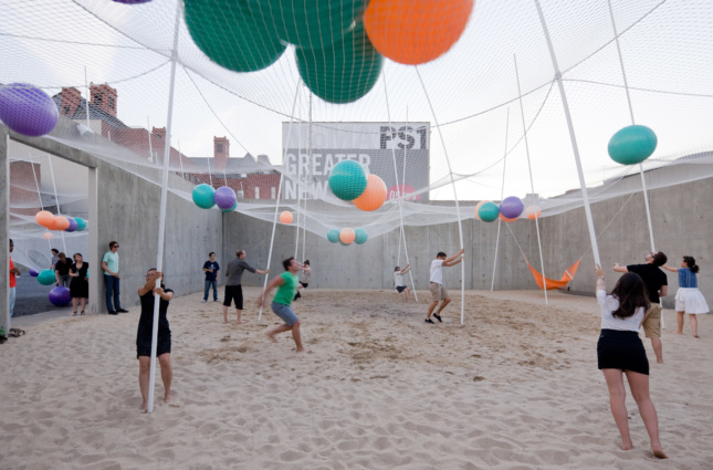 People playing in the sand beneath a net full of beach balls