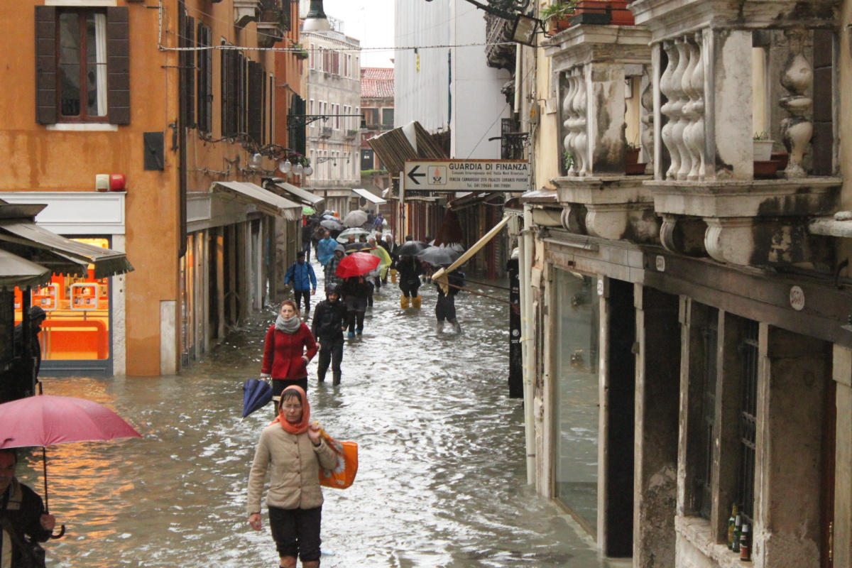People walk through a flooded street in Venice
