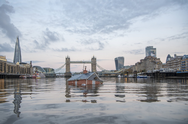 Photo of a house submerged in the River Thames by Extinction Rebellion, with towers in the background
