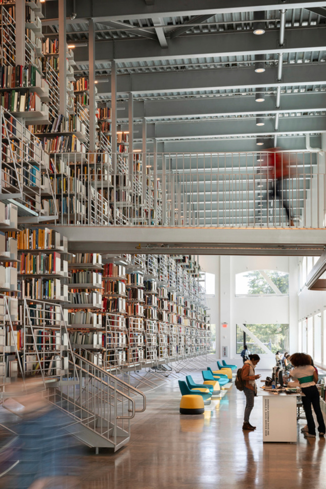 Interior vertical shot of library and people walking on catwalk to book stacks