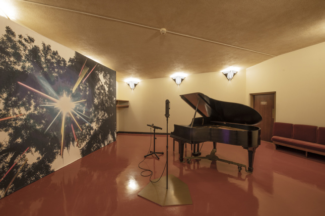 A piano next to a mural of a forest