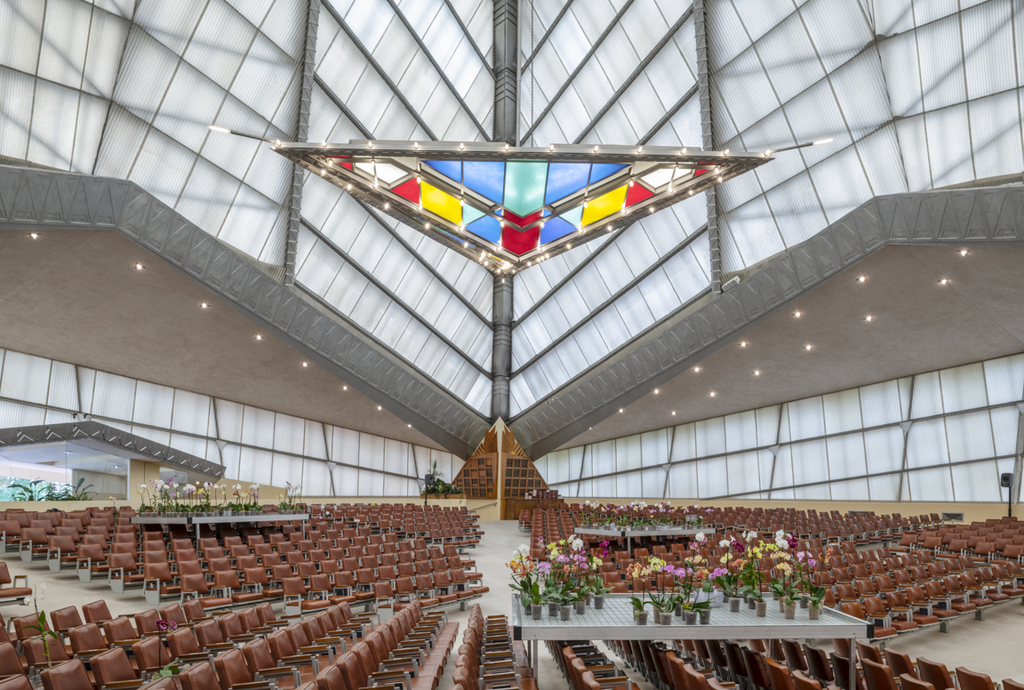 A stained glass triangle hangs under a pyramidal roof over seats and flowers.