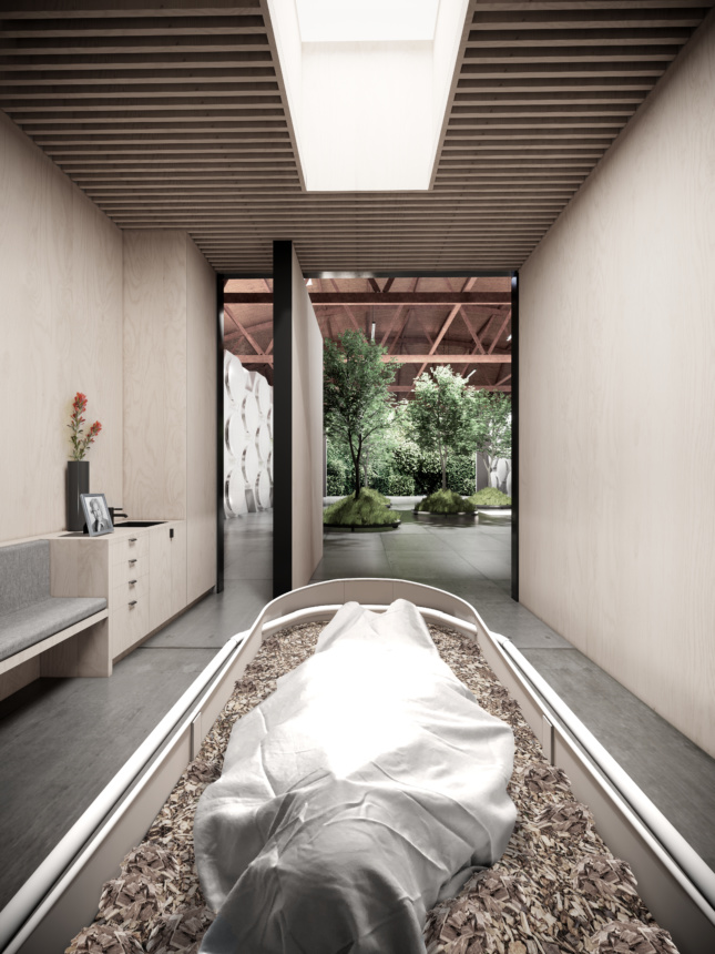 A body is shown in a pale wooden room covered in white and placed in a vessel for decomposition and covered with wood chips. A pivoting door is open in the background showing trees planted in the adjacent room.