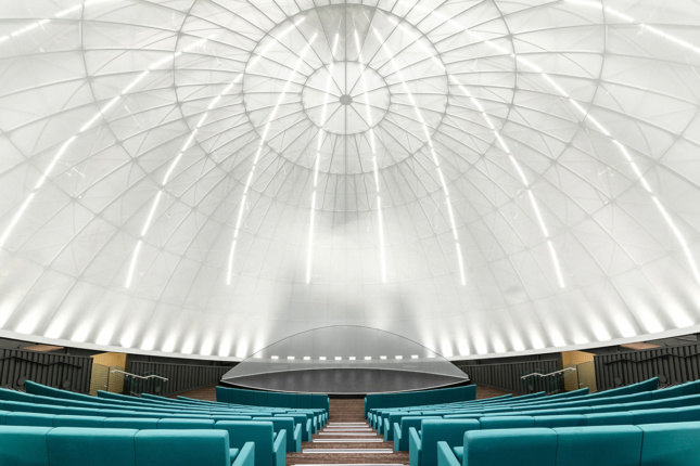 Planetarium ceiling with rows of blue couches