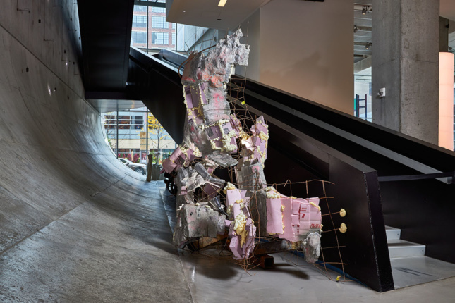 Large-scale mixed media sculpture in situ next to a staircase
